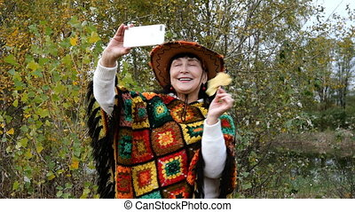 Elegant mature adult woman in colorful clothes vlogs or makes video call on her smartphone, holding it near her face. In autumn park or forest. Medium plan. Outdoors.