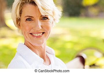 elegant mature woman sitting outdoors
