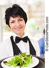 elegant mid age waitress serving salad
