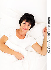 elegant mid age woman lying on bed