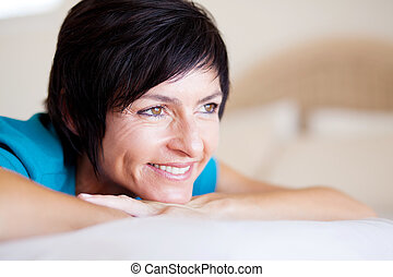 elegant middle aged woman daydreaming