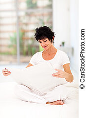 middle aged woman reading newspaper