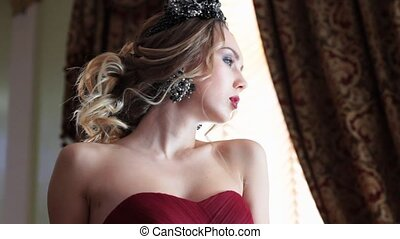 Elegant model leaning on sofa - Young woman in evening red...