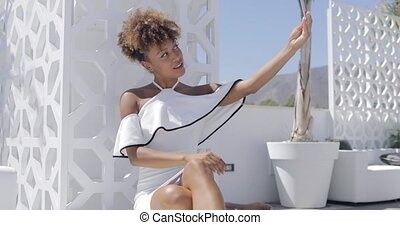 Elegant model relaxing on terrace - Young ethnic woman...