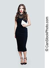 Elegant model woman wearing black dress standing against white wall background