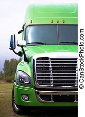 Elegant modern semi truck in green on green parcking lot -...