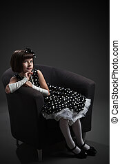Elegant old-fashioned dressed little girl sitting on chair