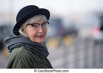 Elegant old woman in hat is posing outdoors