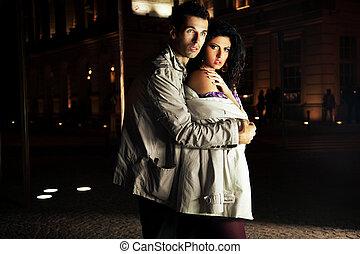 Elegant pair embracing on the night