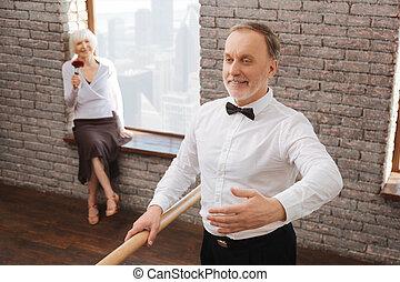 Elegant pensioner acting in the dance studio
