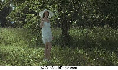 Elegant pretty woman drinking champagne in park