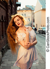 Elegant red haired model with long curly hair wearing white dress posing in evening sunlight