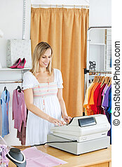 Elegant saleswoman standing at the cash register