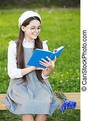 Elegant schoolgirl child girl reading book in park, french language concept