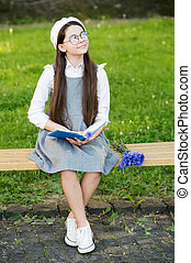 Elegant schoolgirl child girl reading book in park, learn grammar concept