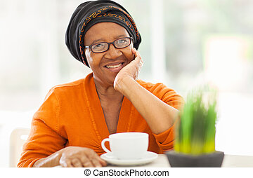 senior african woman having tea