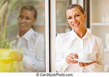 elegant senior businesswoman with coffee