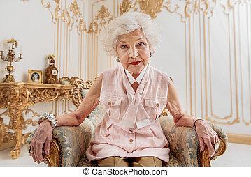 Elegant senior lady relaxing on expensive armchair