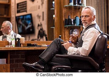 Elegant senior man with whiskey glass and cigar at barbershop