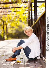 elegant senior woman sitting outdoors