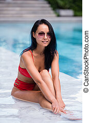 Elegant sexy woman in the red bikini on the sun-tanned slim and shapely body is posing near the swimming pool
