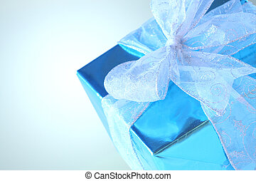 Elegant sky blue colored present with silver ribbons and bow isolated on white.