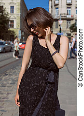 Elegant smiling model wearing fashionable dress and glasses walking on the city streets