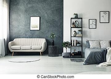Elegant sofa standing by black wall