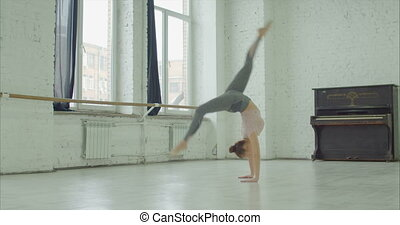 Elegant sporty woman doing cartwheel exercise - Graceful...