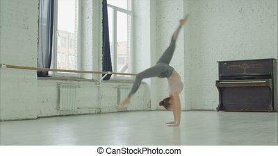 Elegant sporty woman doing cartwheel exercise - Graceful...