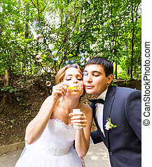 elegant stylish groom and happy gorgeous  bride have fun with bubble blower outdoors in park