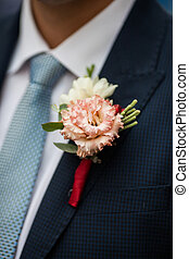Elegant stylish groom in black suit with fresh flower boutonniere closeup