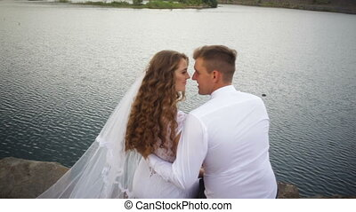 elegant stylish groom with his happy gorgeous brunette bride on the background of a lake