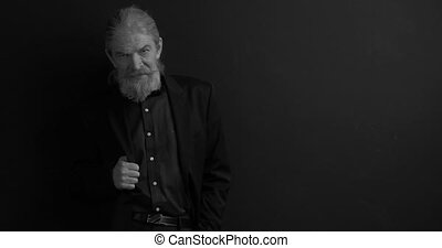 Elegant stylish old business man with piercing gaze in dark business clothes with one hand in chest pocket in semi-lit room on black background. Black and white portrait. Waist portrait. Prores 422.