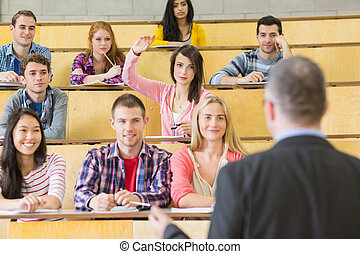 Elegant teacher with students at the lecture hall - Rear...
