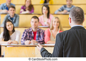 Elegant teacher with students sitting at the lecture hall -...