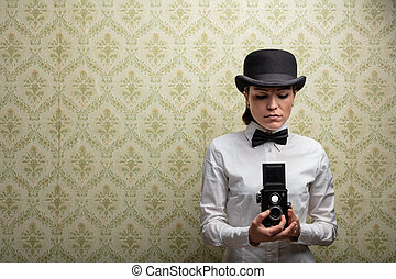 Elegant vintage woman photographer in bowler hat and bow tie...