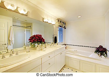 Elegant white bathroom interior decorated with flowers.