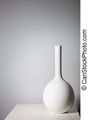 Elegant white vase on a small table against a white wall with copyspace and vignette