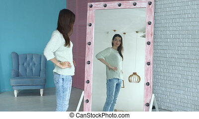 Elegant woman admiring herself reflection in mirror