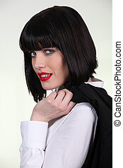 Elegant woman carrying jacket on her shoulder