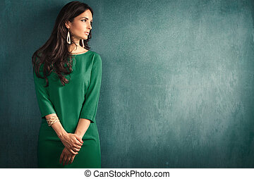 elegant mature woman in green dress lean on wall