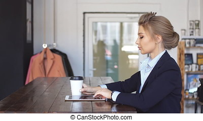Elegant woman holding a coffee and tablet in the modern office