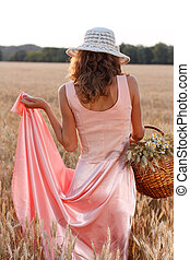 Elegant woman in a dress and hat with basket in the wheat field