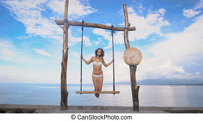 Elegant woman in a good mood and with a good body, dressed in a white swimsuit swinging on a swing on the shore of a sandy beach, on a background of blue and blue calm ocean palates
