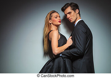 elegant woman in black pulling man's jacket
