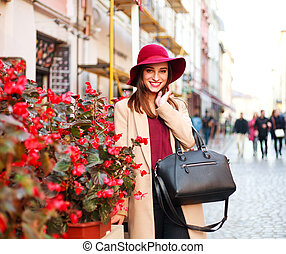 Elegant woman in coat and purple hat on street tourist town with flowers