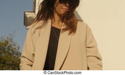 Elegant woman in coat and sunglasses