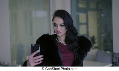 Elegant woman in the fur taking selfie in the restaurant
