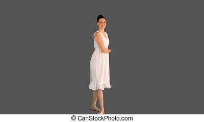 Elegant woman in white dress turnin